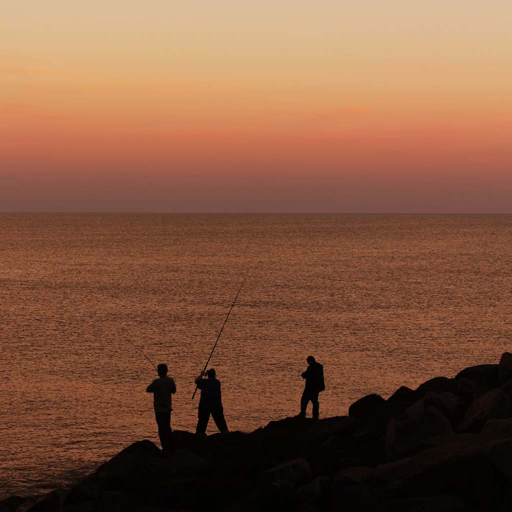 Guys on rocks fishing in sunset red sky