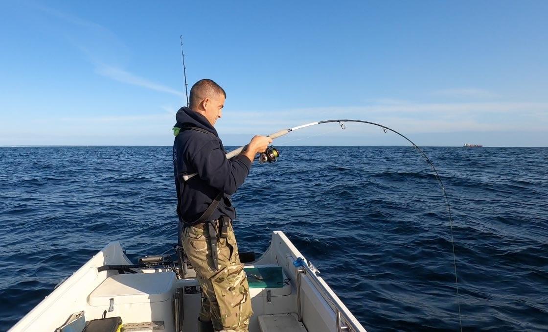 John Fishlocker plays a fish to the boat
