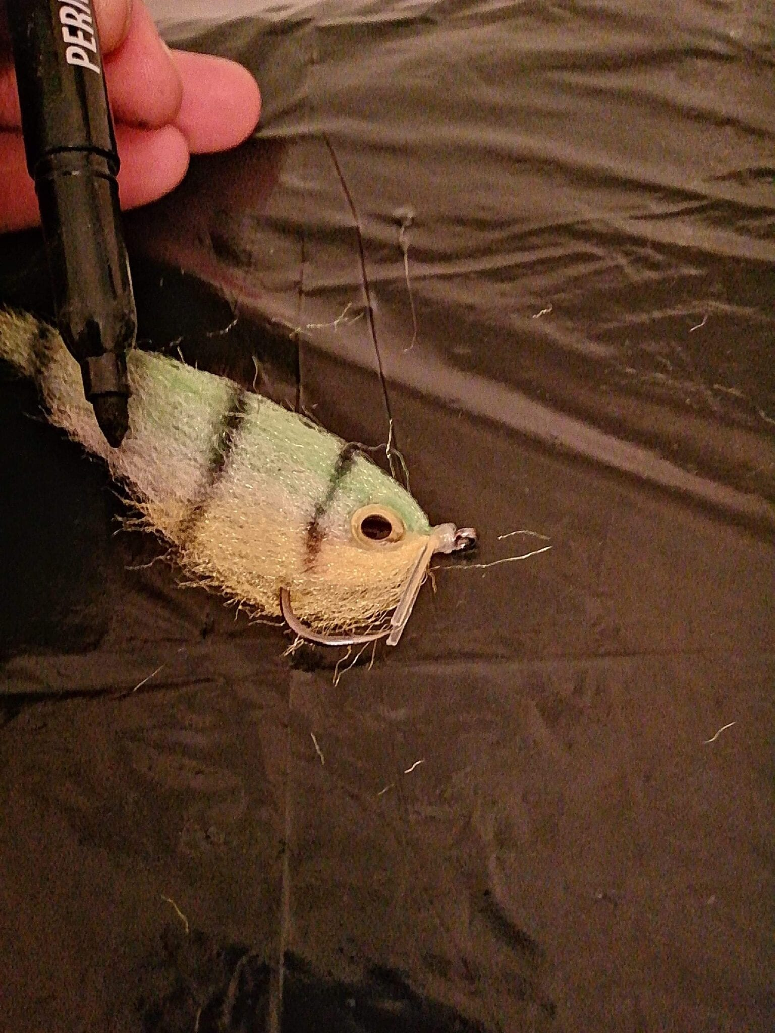 Put the fly flat to add the marker pen and dab lines as this is an easier way to apply the markers to the minnow.